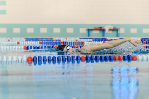 Junge frau in schutzbrillen und mütze schwimmen im vorderen crawl-stroke-stil im blauen wasser-indoor-rennpool.