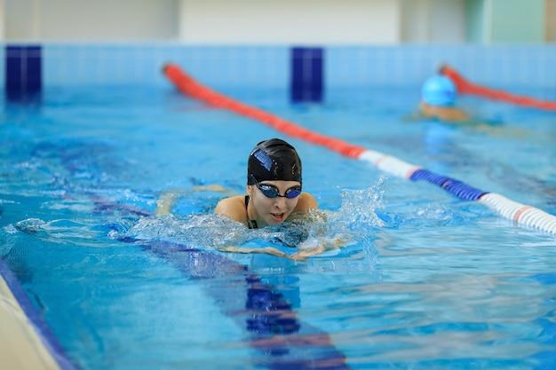 Junge frau in schutzbrillen und mützenschwimmen im brustschwimmen-stil im blauen wasserinnen-rennpool.