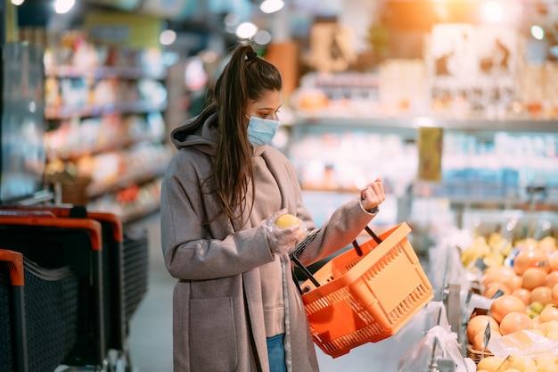 Junge frau in schutzmaske macht einkäufe im supermarkt