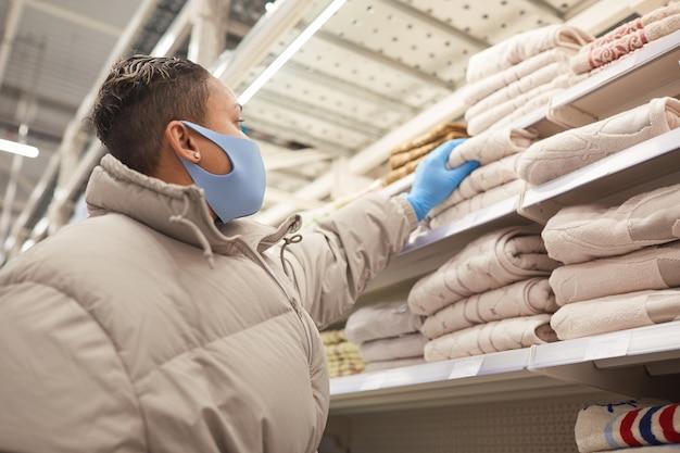 Junge frau in schutzmaske und in handschuhen, die neue handtücher während ihres einkaufs in der pandemie wählen