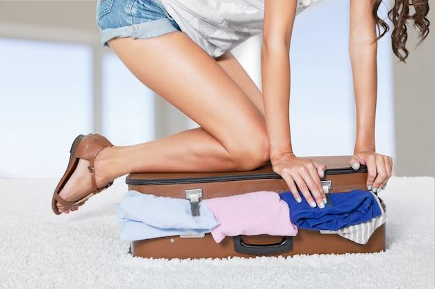 Junge frau in shorts sitzt auf koffer