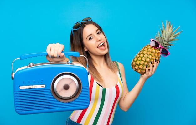 Junge frau in sommerferien über dem blauen hintergrund, der eine ananas mit sonnenbrille hält