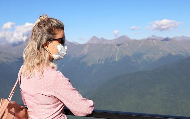 Junge frau in sonnenbrille und maske steht im profil und schaut in richtung der berge