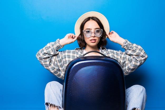 Junge frau in sonnenbrille und strohhut, die nahe einem koffer vor dem flug sitzt.