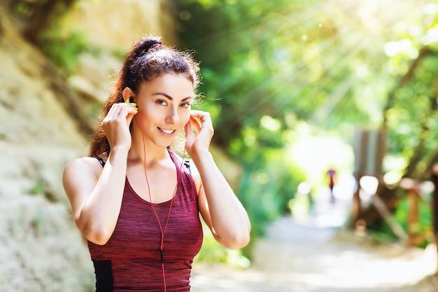Junge frau in sportbekleidung hört musik über kopfhörer, während sie auf der straße trainiert
