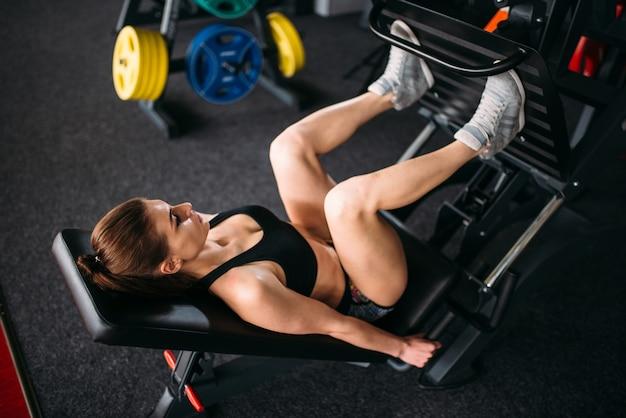 Junge frau in sportbekleidung trainiert auf übungsmaschine in sporthalle. sportlerin training im fitnessclub