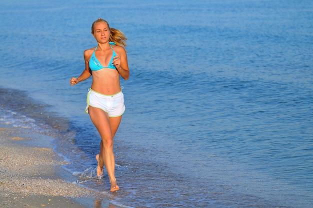 Junge frau in sportbekleidung und turnschuhen, die nahe stillem meeresrand laufen und am sonnigen sommertag lächeln. konzept für glück, urlaub und freiheit
