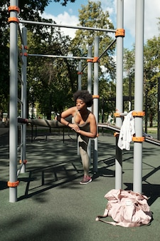 Junge frau in sportkleidung, die morgens durch einrichtungen trainiert