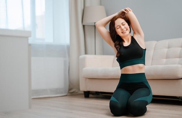 Junge frau in sportkleidung macht dehnübungen zu hause yoga fitness sitzt auf ...