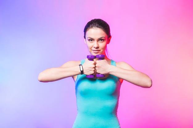 Junge frau in sportkleidung mit schönem lächeln, das gewicht hantel hält fitness-training