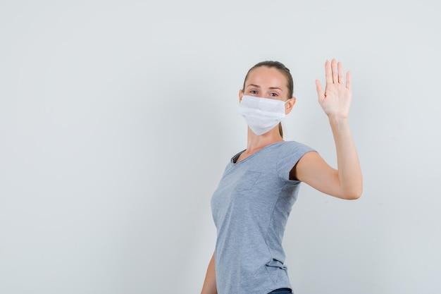 Junge frau in t-shirt, maske, jeans, die hand winkt, um sich zu verabschieden und fröhlich auszusehen.