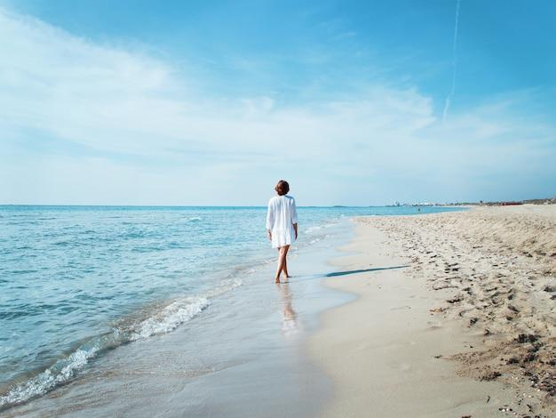 Junge frau in vertuschung am strand entlang spazieren. reise- und urlaubskonzept.