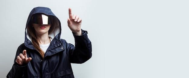 Junge frau in virtual-reality-brille, die finger auf einem touchscreen auf hellem hintergrund drückt. banner.