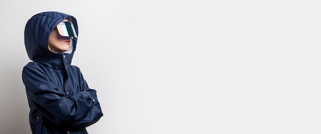 Junge frau in virtual-reality-brille, in einer blauen jacke mit verschränkten armen auf hellem hintergrund. banner.