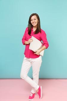 Junge frau in voller länge in rosa hemdbluse, weiße hose mit laptop-pc isoliert auf hellrosa blauer pastellwand..