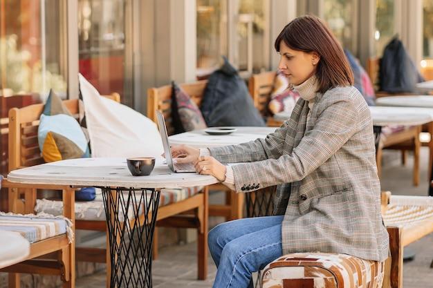 Junge frau in warmem pullover und blazer, die im café auf der terrasse am netbook arbeitet. herbstmorgen. streetstyle.