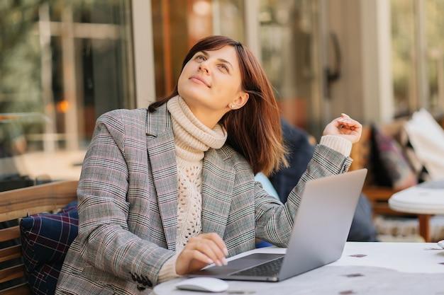 Junge frau in warmem pullover und blazer träumt von etwas mit tragbarem netbook im café auf der terrasse. herbstmorgen. streetstyle.