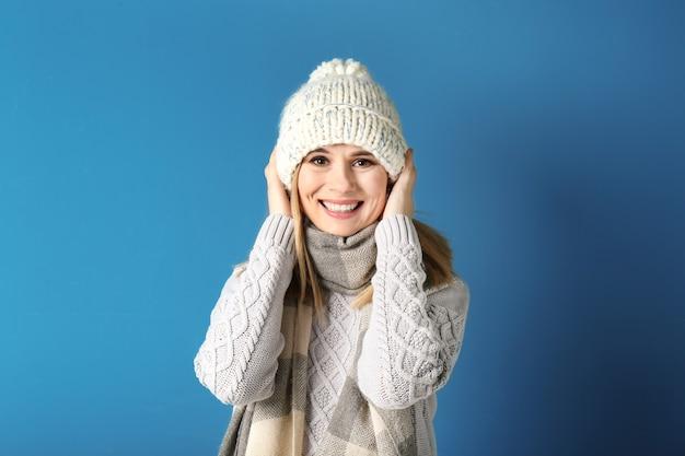 Junge frau in warmer kleidung auf farbhintergrund. bereit für den winterurlaub
