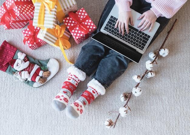 Junge frau in weihnachtsmütze, die online einkauft, umgeben von geschenken draufsicht flach lag