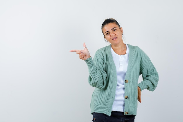 Junge frau in weißem hemd und mintgrüner strickjacke, die mit dem zeigefinger nach links zeigt, während sie die hand an der taille hält und ernst aussieht