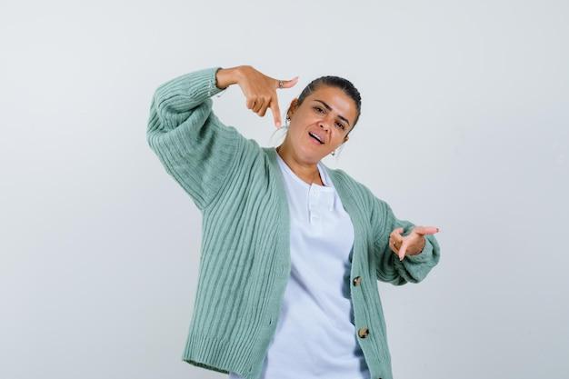 Junge frau in weißem hemd und mintgrüner strickjacke, die mit zeigefingern auf die kamera zeigt und glücklich aussieht