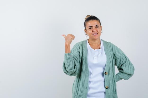Junge frau in weißem hemd und mintgrüner strickjacke, die nach hinten zeigt, während sie die hand hinter der taille hält und glücklich aussieht