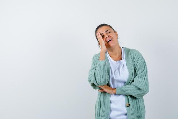 Junge frau in weißem hemd und mintgrüner strickjacke, die sich auf die handfläche lehnt, während sie die hand am ellbogen hält und gehetzt aussieht