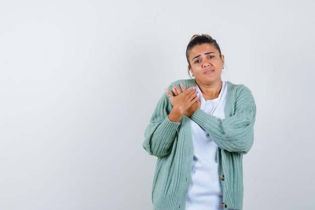 Junge frau in weißem hemd und mintgrüner strickjacke, die sich die hände reibt und gehetzt aussieht