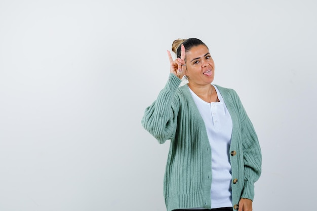 Junge frau in weißem t-shirt und mintgrüner strickjacke, die rock'n'roll-geste zeigt, die zunge herausstreckt und glücklich aussieht