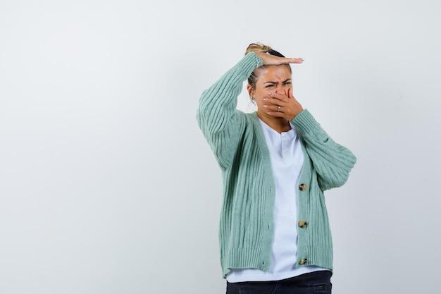 Junge frau in weißem t-shirt und mintgrüner strickjacke, die wegen schlechten geruchs die nase kneift und genervt aussieht