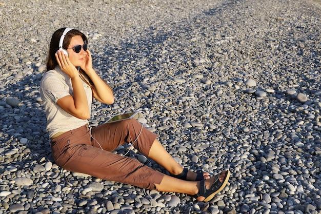 Junge frau in weißen kopfhörern hört musik, während sie auf kieselsteinen sitzt