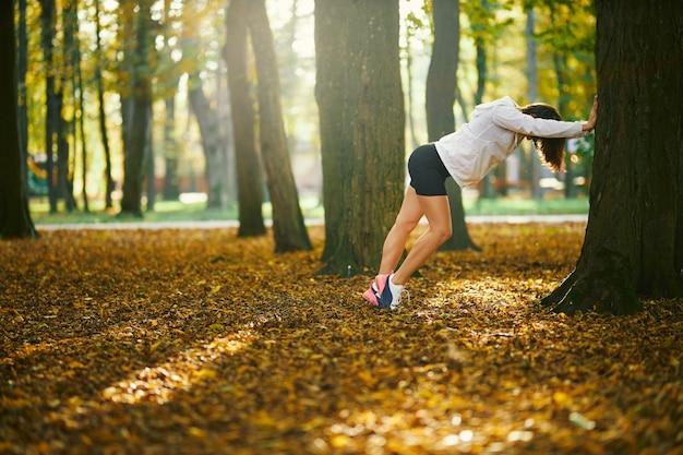 Junge frau in weißer sportjacke und shorts, die körper in der nähe von baum im park ausdehnt. sportliche brünette macht morgengymnastik im freien. konzept des aktiven gesunden lebensstils.