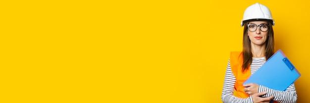 Junge frau in weste und schutzhelm hält ein klemmbrett auf einem gelben