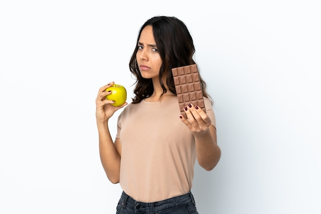 Junge frau isoliert, die eine schokoladentafel in einer hand und einen apfel in der anderen nimmt