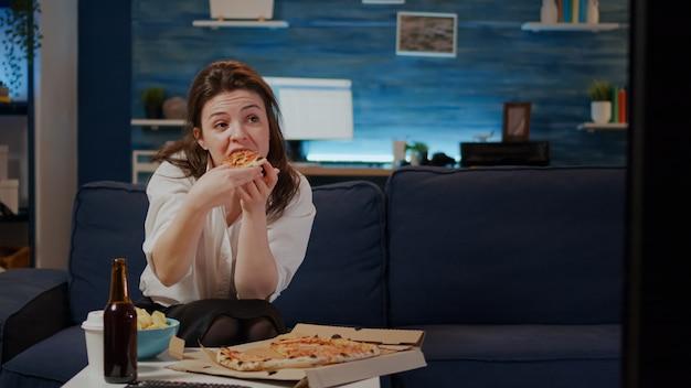 Junge frau isst ein stück pizza aus der kiste und trinkt bier