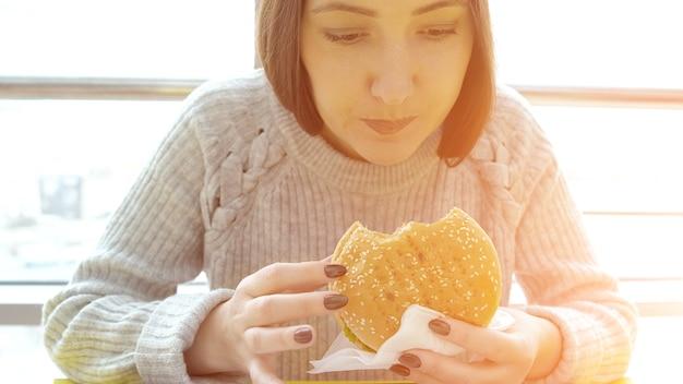Junge frau isst einen burger, sonnenlicht. schädliche fetthaltige lebensmittel.
