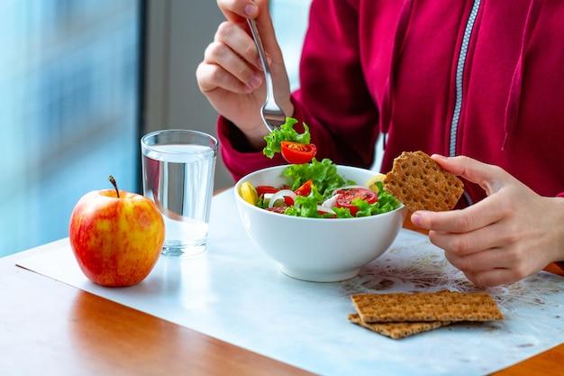 Junge frau isst einen gesunden, frischen gemüsesalat mit knusprigem roggenbrot. diät und gesunder lebensstil konzept. diätessen. richtige ernährung und richtig essen