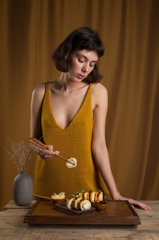 Junge frau isst und genießt frische sushi-rolle mit lachs mit stäbchen auf gelbem hintergrund and