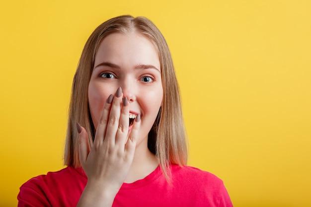 Junge frau ist angenehm überrascht. blondes mädchen im teenageralter bedeckte ihren offenen mund mit der hand überrascht. positives emotionales porträt der jungen frau auf der gelben wand der farbe mit kopienraum.