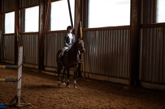 Junge frau ist im pferdesport tätig und trainiert zu pferd