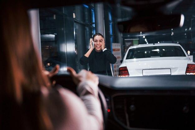 Junge frau ist in einem brandneuen modernen auto, das dem mädchen die hand vor sich hält.