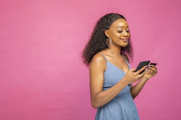Junge frau kauft online mit ihrem smartphone und einer kreditkarte ein