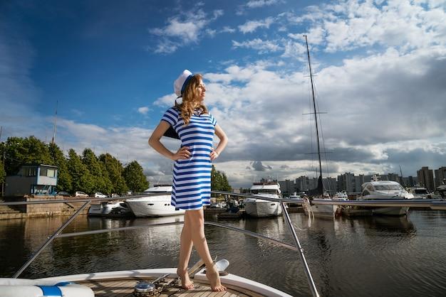 Junge frau kaukasischer abstammung in einem kurzen kleid mit blauen streifen und einer mütze auf einer yacht posiert auf...