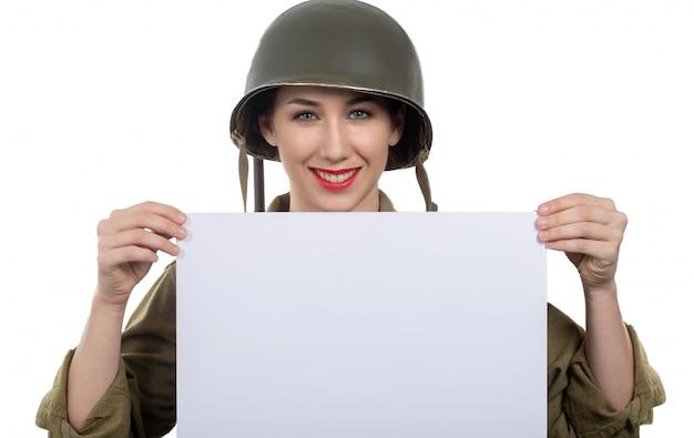 Junge frau kleidete in der wwii-militäruniform mit dem sturzhelm an, der leeres leeres schild mit copyspace zeigt