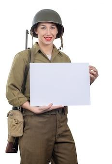 Junge frau kleidete in der wwii-militäruniform mit dem sturzhelm an, der leeres leeres schild zeigt