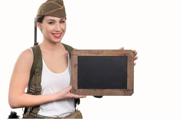 Junge frau kleidete in der wwii-militäruniform mit der kappe an, die leere leere tafel mit einem kopienraum zeigt