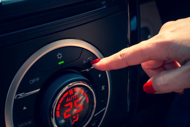 Junge frau klickte auf die automatische taste des bedienfelds der automatischen klimaanlage