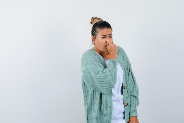 Junge frau kneift die nase wegen schlechten geruchs in weißem hemd und mintgrüner strickjacke und sieht gehetzt aus