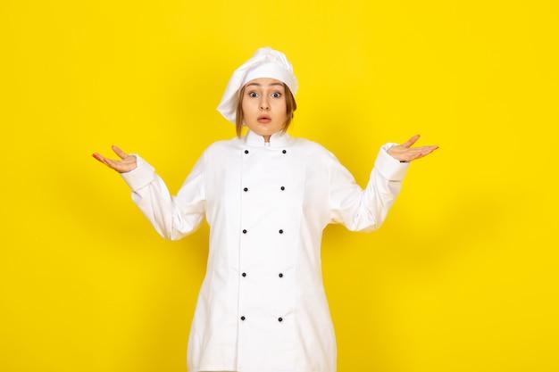 Junge frau kocht im weißen kochanzug und im weißen überraschten ausdruck der mütze