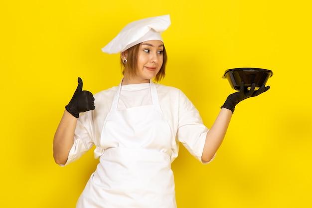 Junge frau kocht im weißen kochanzug und in der weißen kappe in den schwarzen handschuhen, die schwarze schüssel zeigen